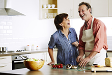 Couple Laughing and Cooking in Kitchen
