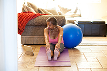 Woman with Yoga Ball Stretching in front of tablet